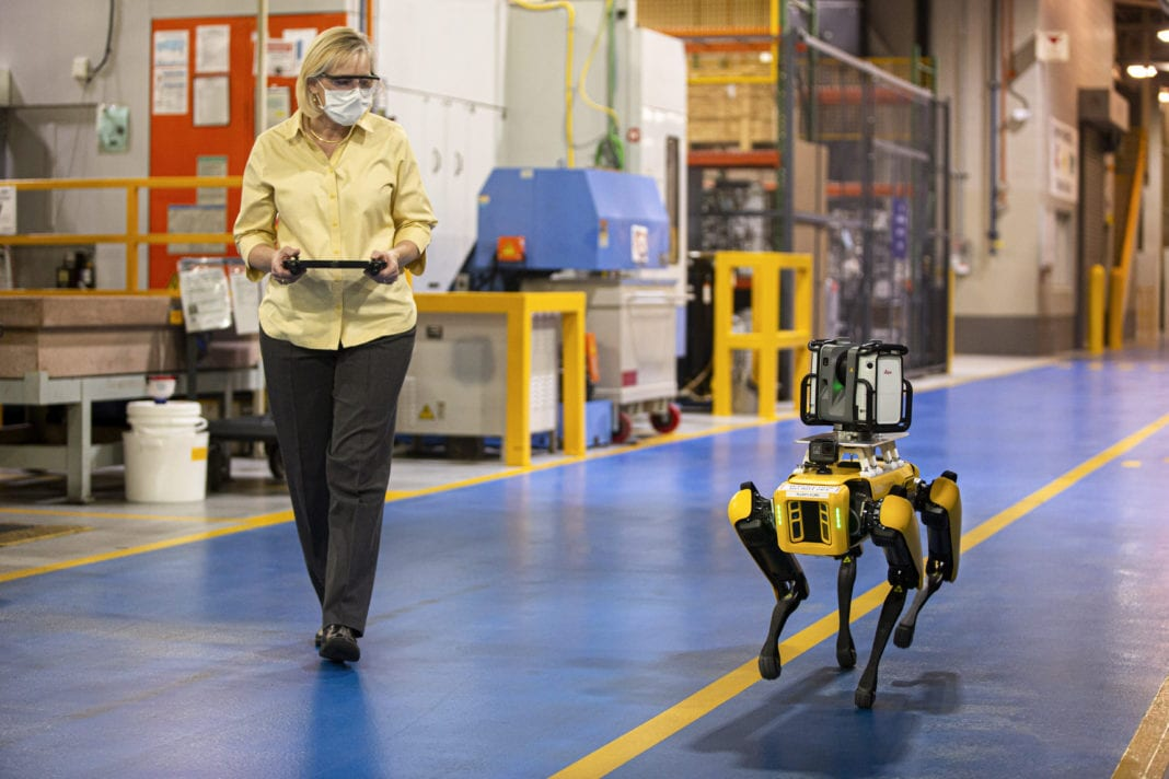 Paula Wiebelhaus, Fluffy's handler, navigates Fluffy, the dog-like robot, through the plant. Ford is tapping four-legged robots at its Van Dyke Transmission Plant in early August to laser scan the plant, helping engineers update the original computer-aided design. These robots can be deployed into tough-to-reach areas within the plant to scan the area with laser scanners and high-definition cameras, collecting data used to retool plants, saving Ford engineers time and money. Ford is leasing two robots, nicknamed Fluffy and Spot, from Boston Dynamics – a company known for building sophisticated mobile robots.